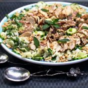 asian cabbage salad with grilled chicken, cucumbers and mint on a large round platter
