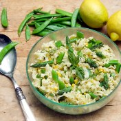 lemony frilly pasta with sugar snap peas and corn in a clear glass bowl