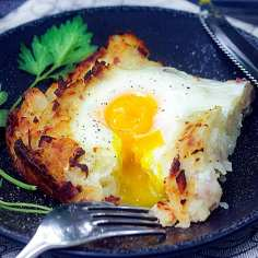 one slice of Swiss Rosti on a black plate - shredded potato casserole with an egg baked on top