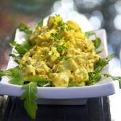 curried chicken salad on a rectangular white platter garnished with arugula leaves