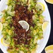 oval platter with shredded Brussels sprouts topped with fried shallots