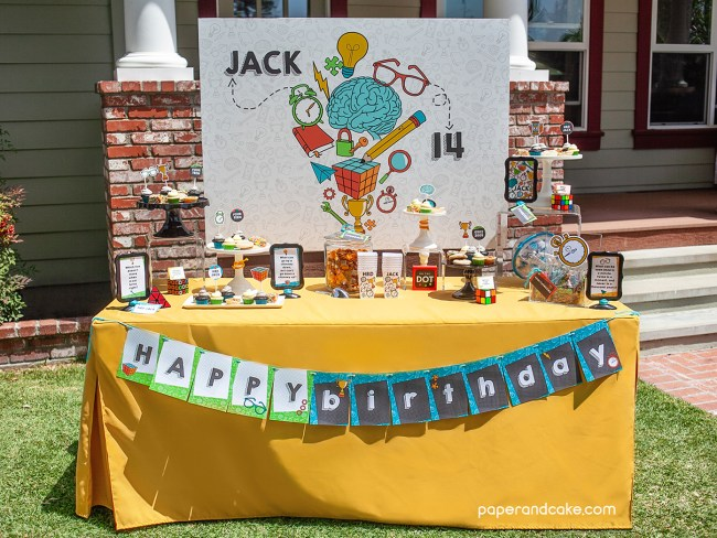 Birthday party dessert table with bright yellow table cloth on a bright sunny day
