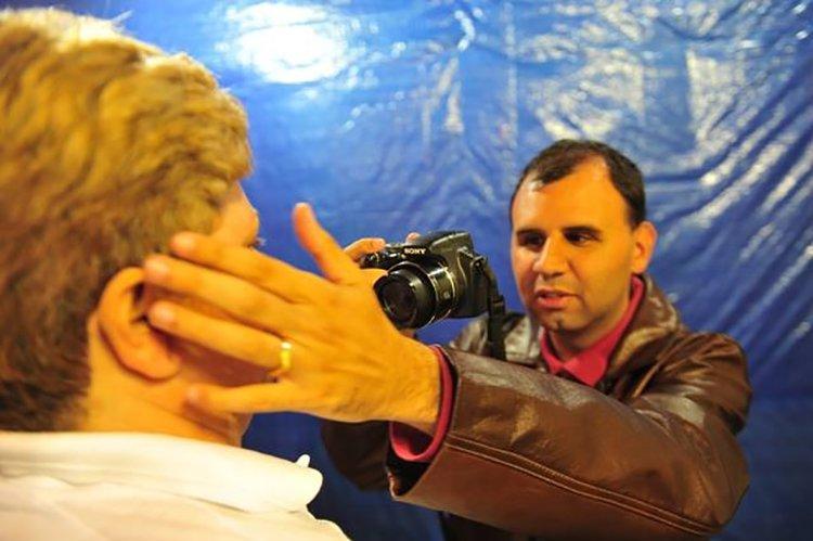 Teco Barbero em ação durante um retrato. Descrição da Imagem: Teco Barbero toca o rosto da pessoa a ser fotografada para realizar o retrato.