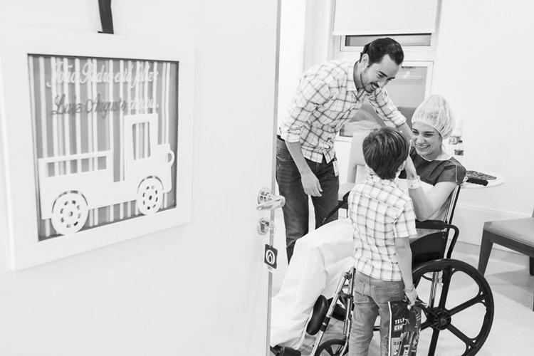 Foto: Grazi Ventura. Descrição da imagem: Os pais e o filho mais velho do casal, estão no quarto do hospital preparados para o parto, e na porta do quarto tem um quadro de identificação com o nome do bebê.