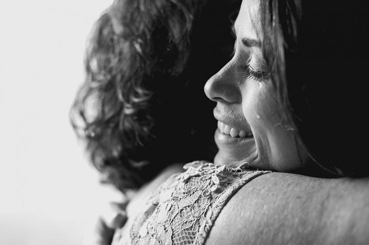 Foto: Flávio Iwai. Descrição da imagem: A filha (noiva) com uma lágrima escorrendo pelo rosto abraça a mãe em seu casamento.