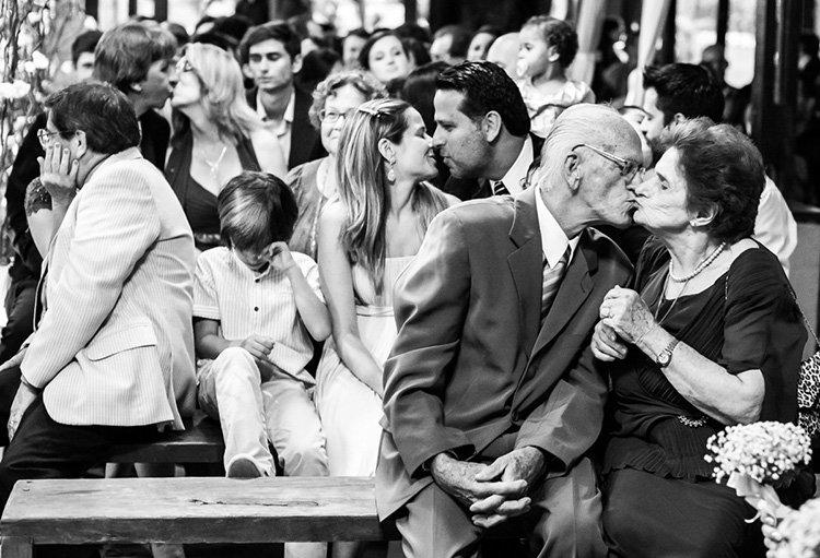Foto: Flávio Iwai. Descrição da imagem: Os convidados do casal se beijam durante a cerimônia a pedido do padre.