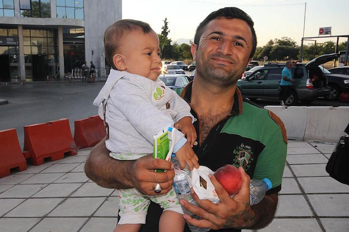 Refugee Solidarity Movement Thessaloniki offers a Syrian refugee and his infant food and basic supplies.
