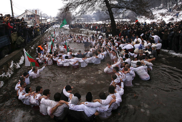 Bulgarian men dance in the icy waters of the Tundzha river during a celebration for Epiphany Day in the town of Kalofer in Bulgaria