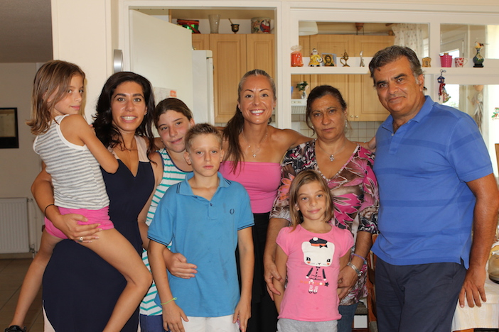 Voula, center, in pink, visiting with children and staff at SOS Children's Villages in Greece.