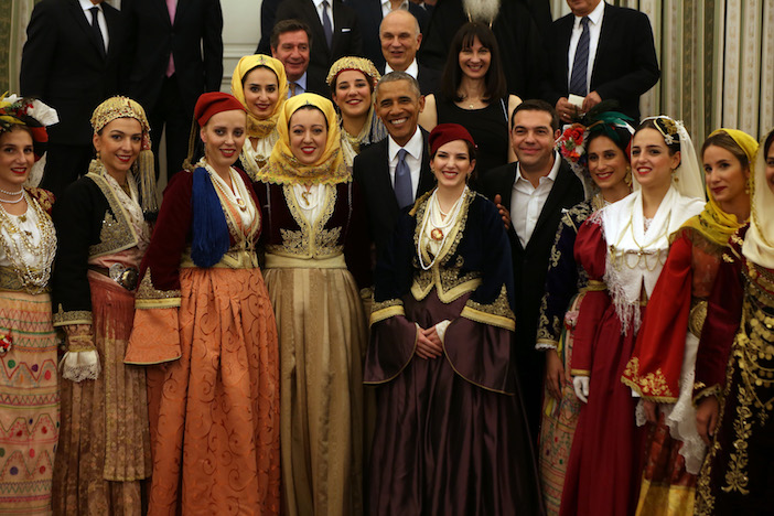 Women dressed in traditional costumes from throughout Greece greet President Obama at the State Dinner held in his honor.
