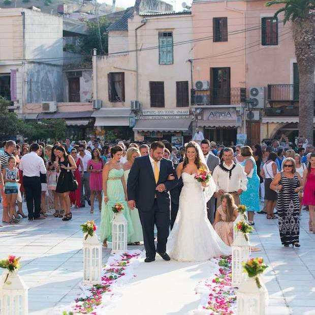 In the old town of Hania, the couple walks on the flowered pathway as family and friends watch.