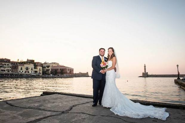 The couple posing at the Venetian harbor of Hania with the imposing lighthouse in the background