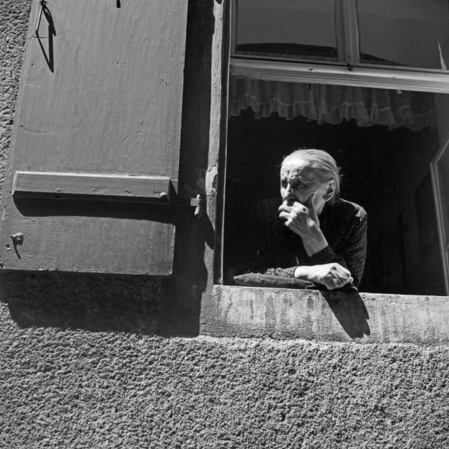 Eine alte Frau schaut aus ihrem Fenster heraus in Regensburg, Deutschland 1930er Jahre. An old woman watching out of her window at Regensburg, Germany 1930s.