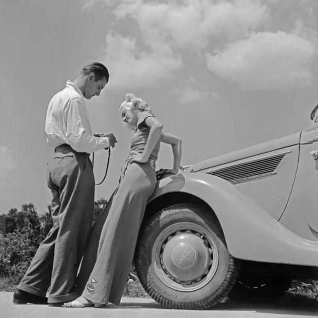 Eine Frau und ein Mann an der Motorhaube eines Ford V8, Deutschland 1930er Jahre. A woman and a man at the bonnet of a Ford V8, Germany 1930s.
