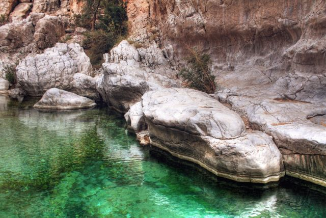38436537 - detail of emerald green water in wadi bani khalid with large boulders, outside of muscat, oman