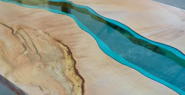 Er stroomt een rivier van glas door deze handgemaakte houten tafels