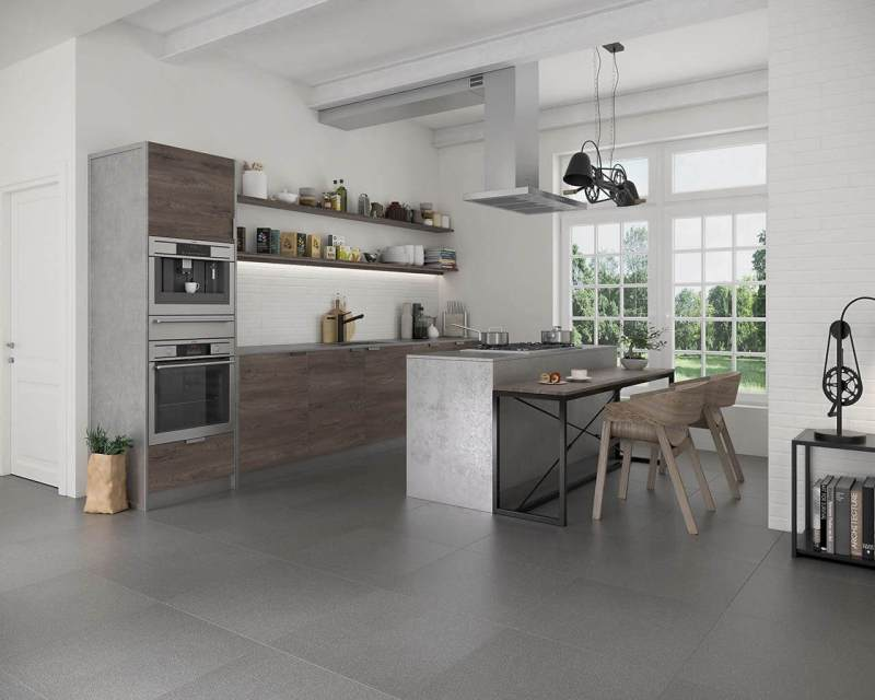 Raw loft-style kitchen - ceramics resembling a white brick on the walls and a universal grey, reminiscent of a concrete floor on the floor.