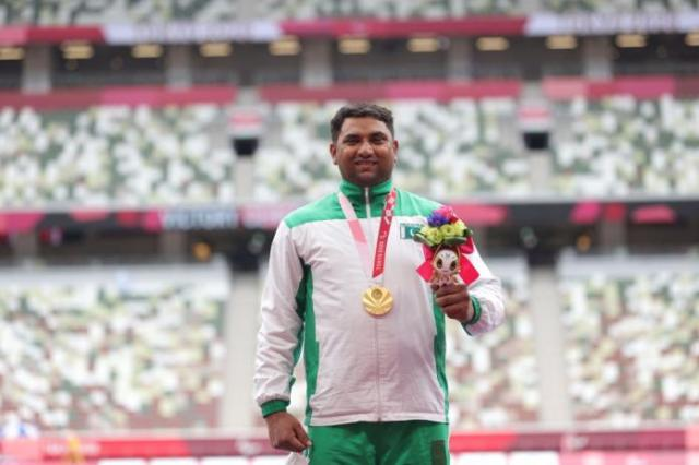 A man with a gold medal in a stadium