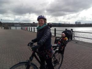 Aggie cycling with demo doll in bike seat
