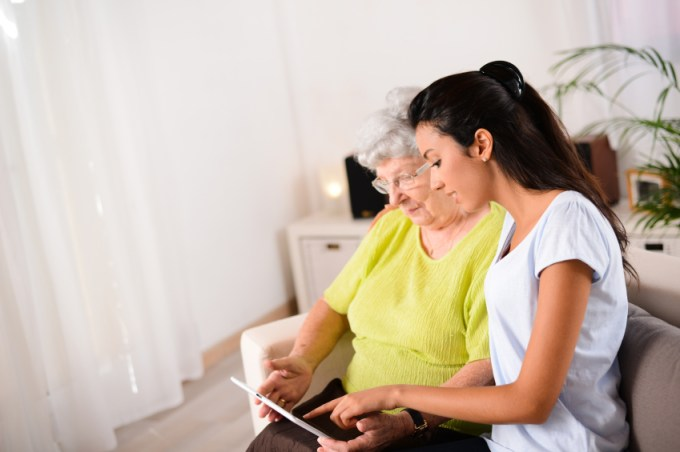 cheerful young girl with elderly woman playing with digital tablet at home