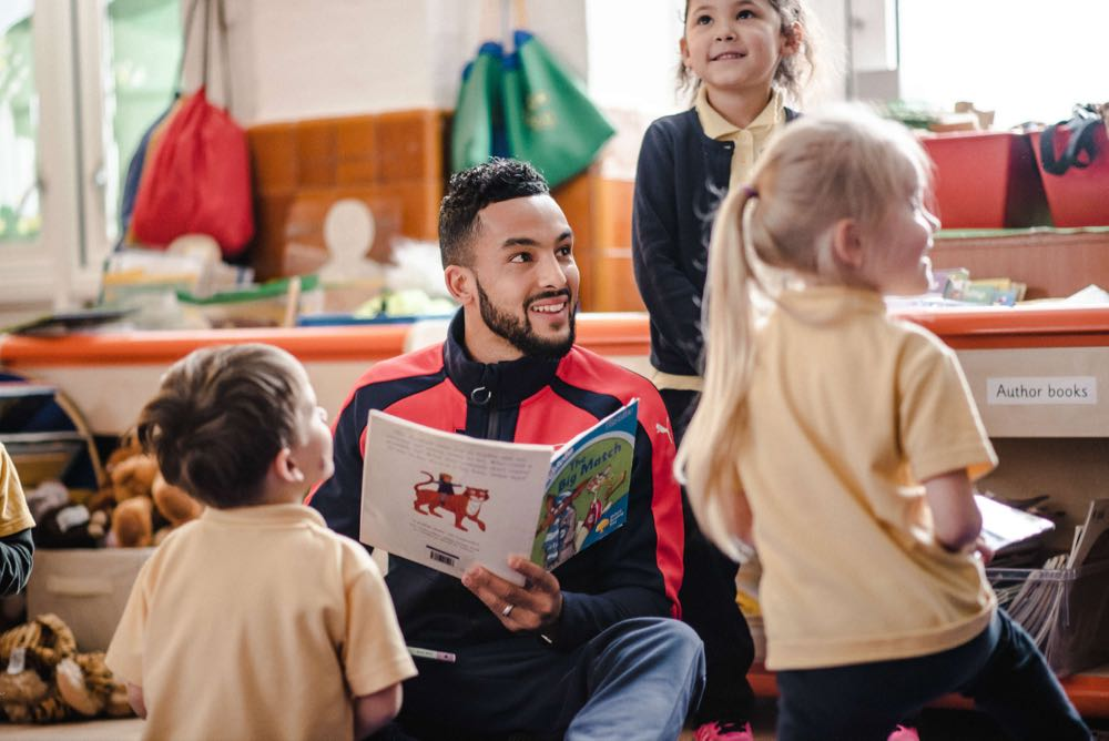 Theo Walcott reading to children in school as part of the Premier League Primary Stars Programme