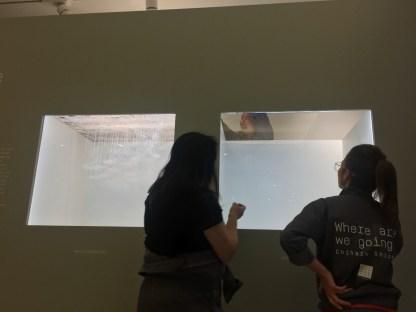 Chiharu Shiota vérifiant l'installation des maquettes dans les petites vitrines de l'entrée Bac-Babylone © Isabelle Henricot