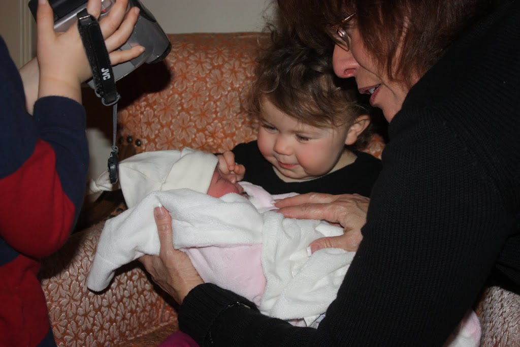 Baby Juliette Élisabeth being held by big sister surrounded by relatives