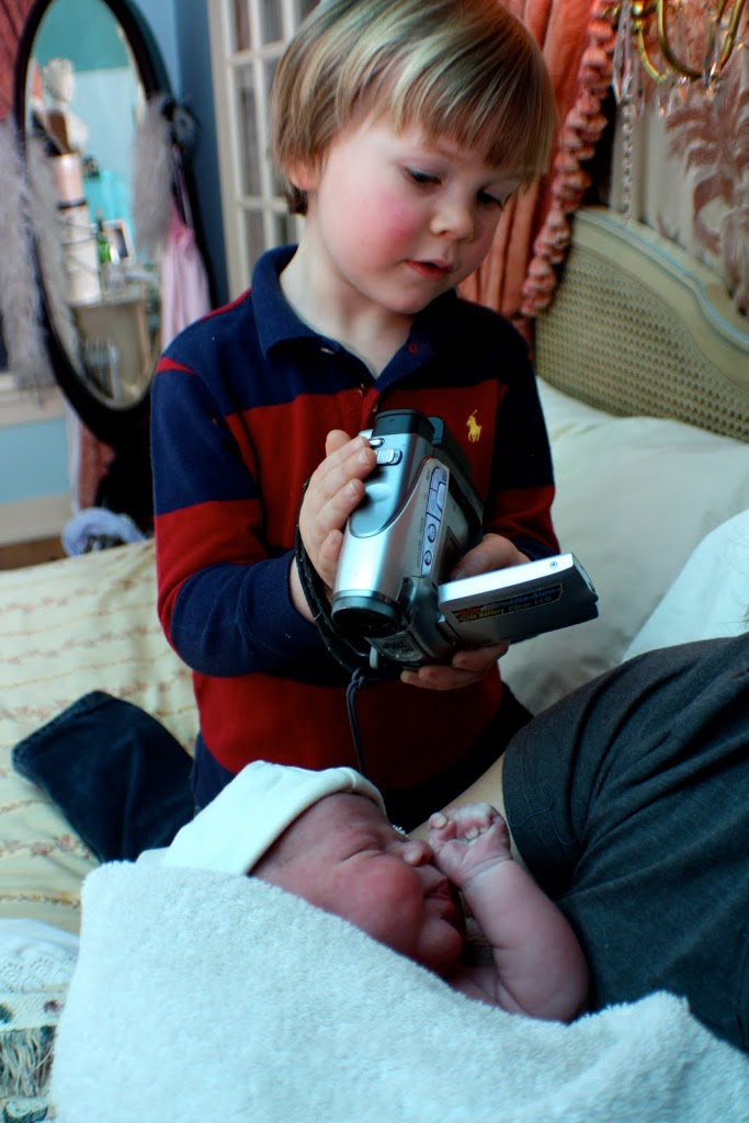 boy filming new baby with a video camera