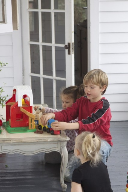 kids playing with farm toys on the Parisienne Farmgirl porch