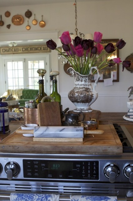 vase with tulips over stove with kitchen accoutrements