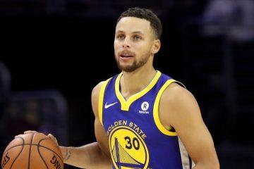 Stephen Curry, balle en main, sous le maillot des Warriors.
