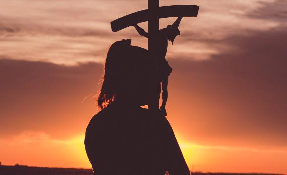 Una chica porta un crucifijo en alto al amanecer