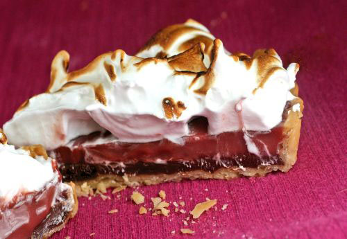 Pomegranate Meringue Tarts. Silky pomegranate curd atop a spicy chocolate ganache in a flaky, buttery crust, topped with loads of meringue!