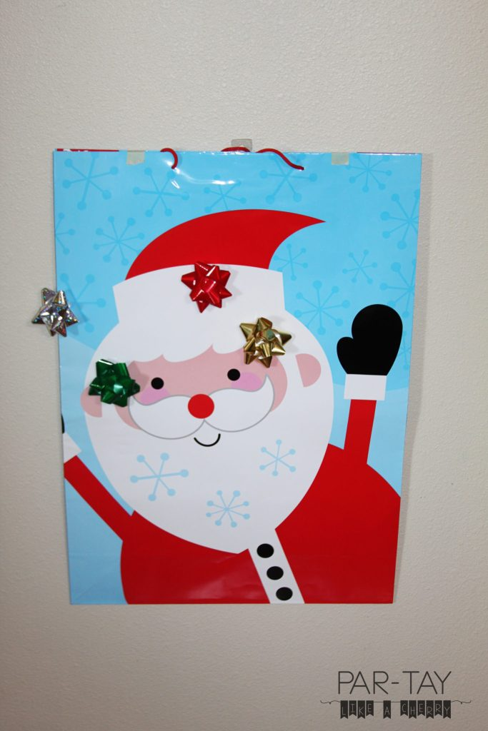 pin the nose on santa toddler christmas party game, just use a giant gift bag and gift bows!