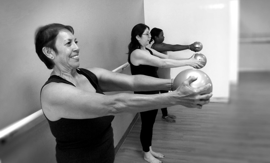 Ladies sculpting arms with medicine balls at Passion Barre black and white