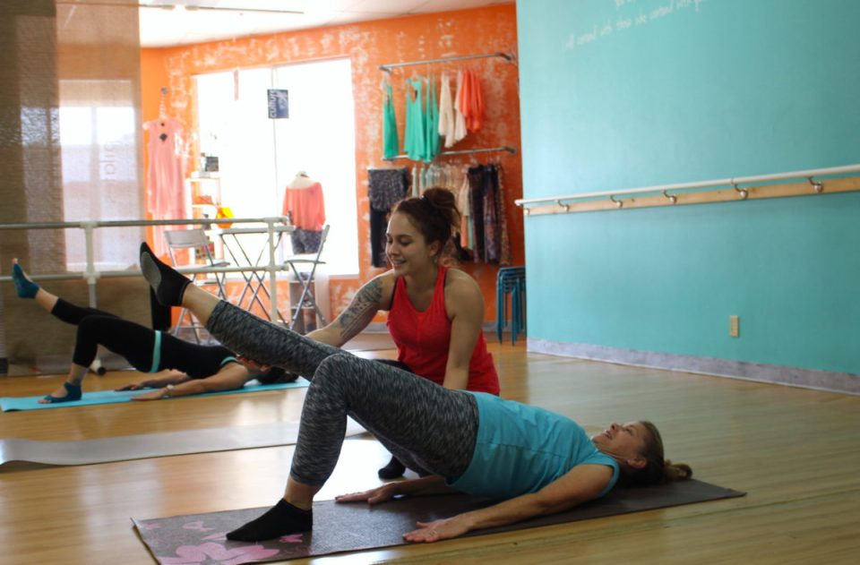 Passion Barre Instructor guides client in Pelvic Stabilizing and glue firming exercise