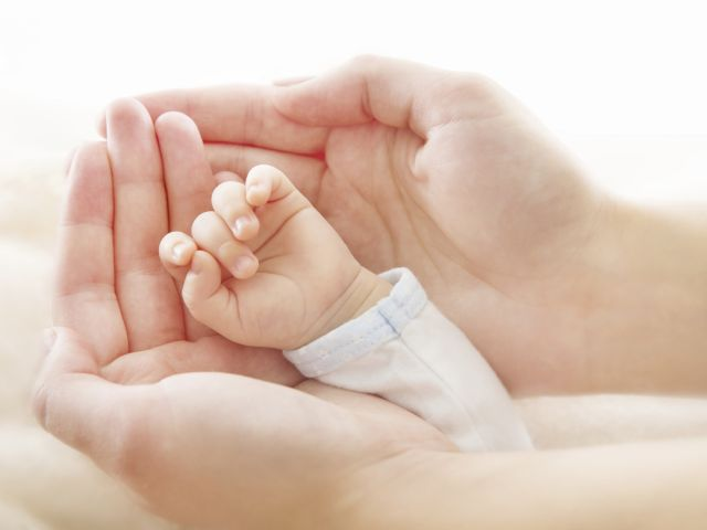 Newborn baby hand in mother hands. Help asistance concept