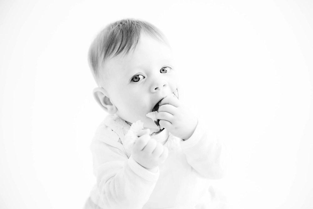 in die Kamera schauendes Kleinkind, dass dabei die Blüten probiert in schwarzweiß - Familienbilder, Familienfotos, Familienfotografie, Kinderfotografie, Kinderfotos, Sitter Session, Sitzalter- Fotos