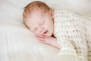 Newborn, Newbornfotografie eines kleinen Jungen in cremefarbenen Tüchern, Neugeborenes, Baby- und Familienbilder