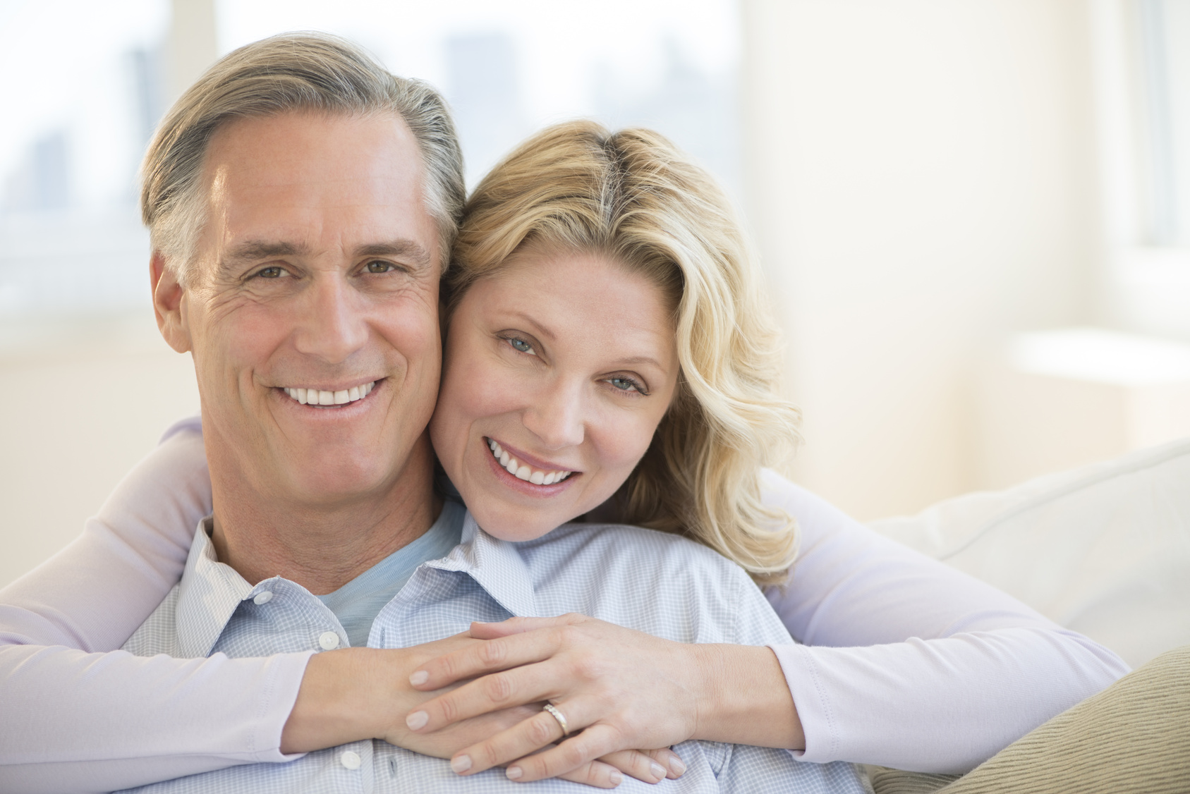 Portrait of loving mature woman embracing man from behind at home