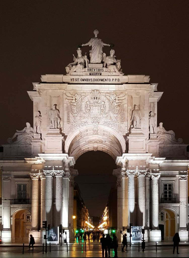Things to do in Lisbon: Rua Augusta Arch lit up at night facing towards the statues at the top.