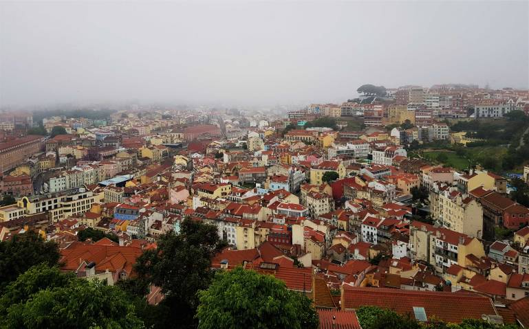 View across the clay coloured roofs from St George's Castle, Lisbon towards the Tagus River, hidden by cloud.