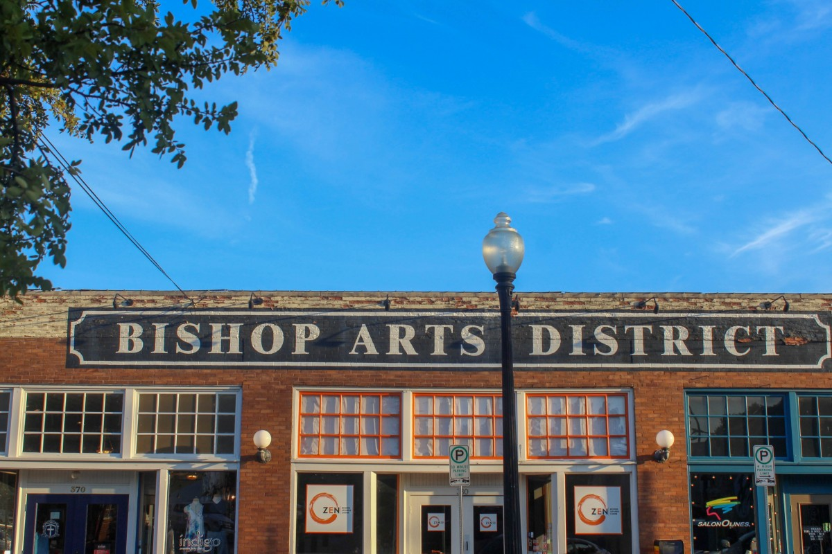 This sign says Bishop Arts District in white lettering above a black label. The shops below are Indigo, Zen, and Salon.