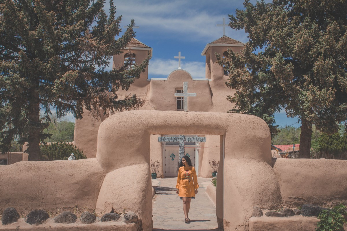 Girl in yellow dress walking in front of San Francisco De Asis Church in Ranchos De Taos, one of the last stops between a Santa Fe to Taos road trip.