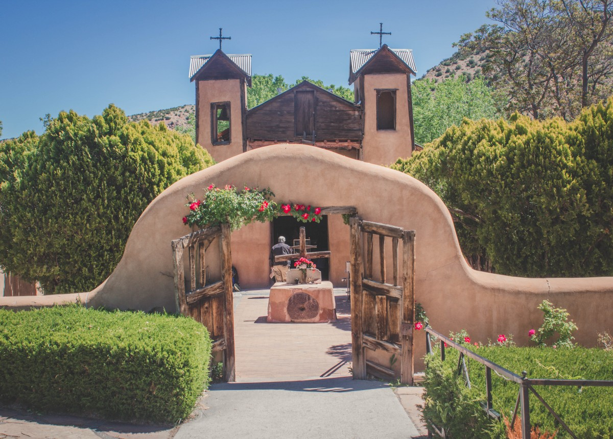 Gorgeous entrance to El Santuario De Chimayo, with flowers and greenery all around. The brick is a pretty shade of brown. And the gates look rustic.