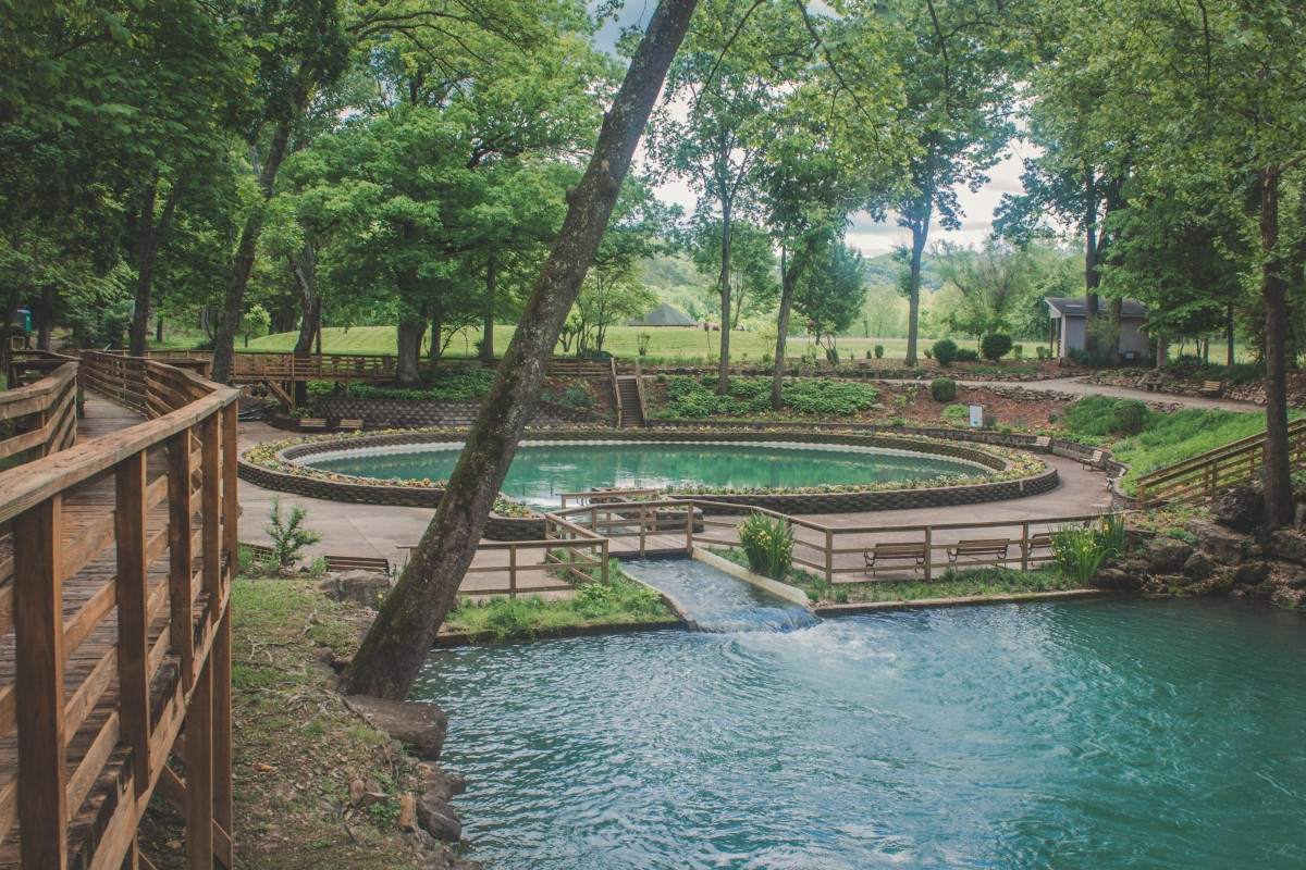 Actual Blue Spring Arkansas. The full circle of the spring is shown with a rim of potted flowers surrounding it.