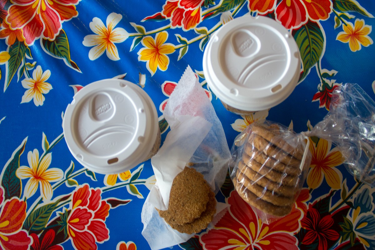 a packet of biscochitos and two cups of coffee on a colorful floral placemat.