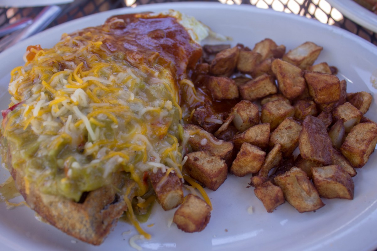 blue corn waffles slathered in red and green chile and a side of potatoes is a traditional New Mexican breakfast