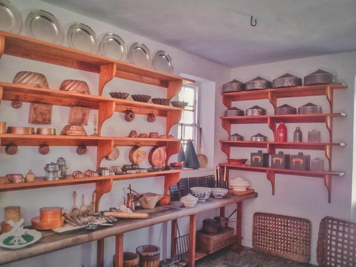 Shelves of plates and pans and cooking utensils line this building in Colonial Williamsburg.