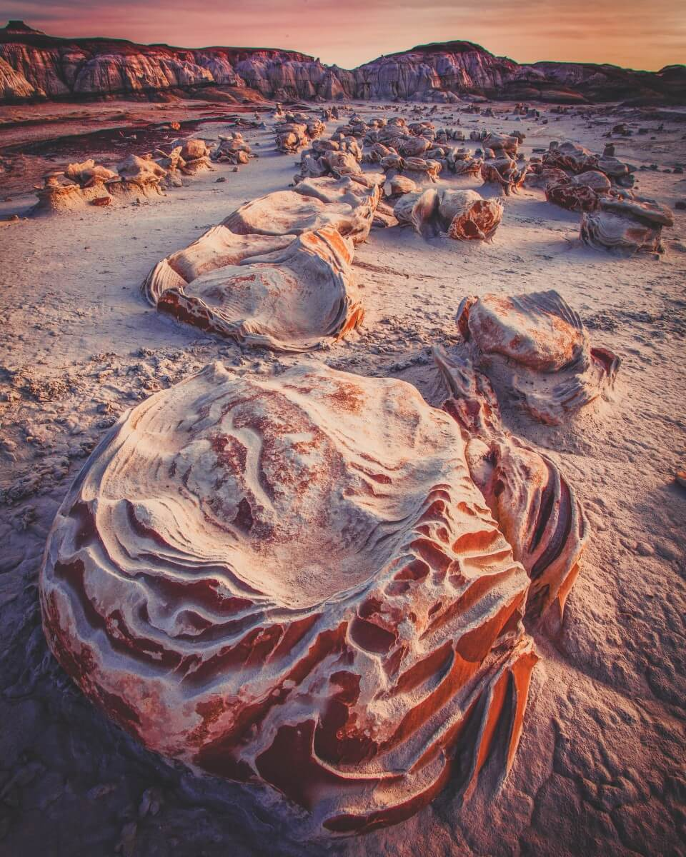 Bisti badlands rock formations are weird and wild. It's sandy colored with deep orange hues thrown in.